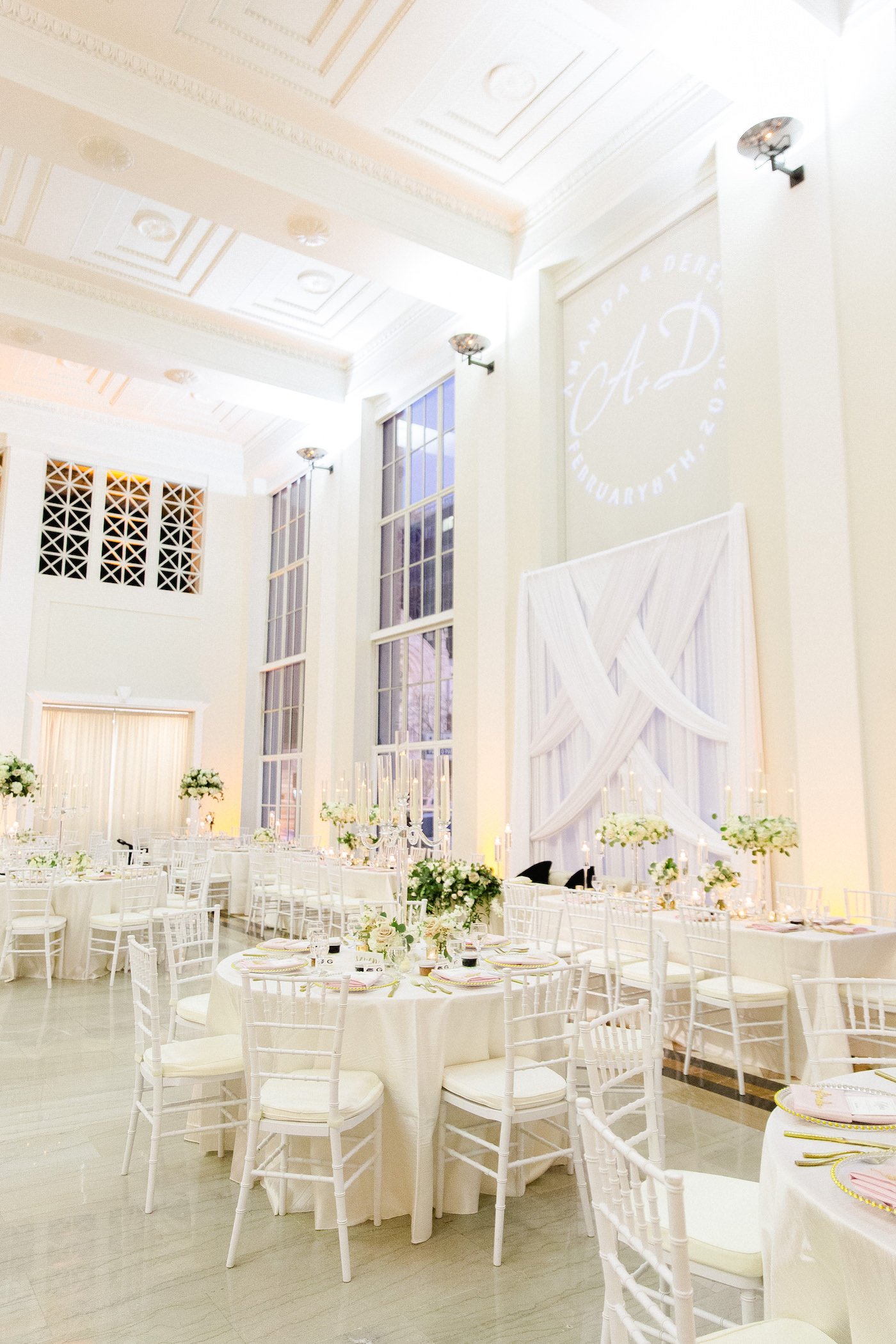 Elegant Classic Wedding Reception and Decor, White Criss Cross Draping and Custom Monogram Gobo Light as Backdrop for Sweetheart Table, Lush Greenery, Ivory Linens, Tall Candelabra Centerpieces with Greenery and Flowers, White Chiavari Chairs | Downtown Tampa Wedding Venue The Vault | Florida Wedding Planner Breezin' Weddings
