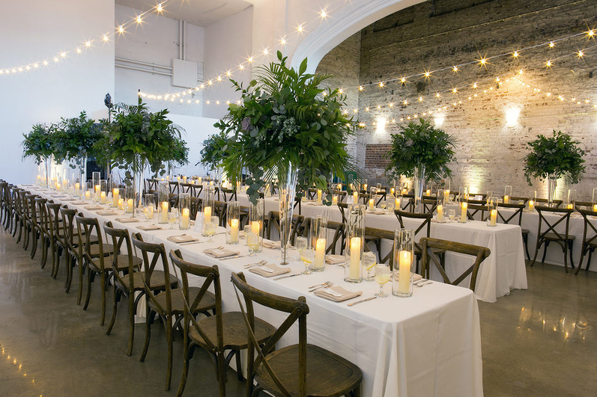 Wes Anderson Inspired Wedding Reception Decor, Long Feasting Tables with Wooden Cross back Chairs, Tall Greenery Plants Centerpieces and String Lights, Hurricane Glass Candles   Wedding Photographer Carrie Wildes Photography   Tampa Bay Wedding Venue The Rialto Theatre   Wedding Planner UNIQUE Weddings and Events   Wedding Florist Monarch Events and Design   Olympia Catering
