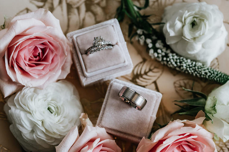 Wedding Rings Shot with Diamond Solitaire Engagement Ring and Platinum Mens Band in Blush Pink Velvet Boxes with Fresh Roses and Ranunculus