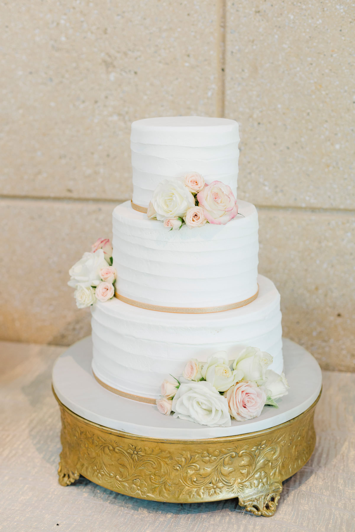 Three Tier Buttercream Wedding Cake accented with Blush Pink and White Roses on Round Gold Ornate Cake Stand | Alessi Bakery