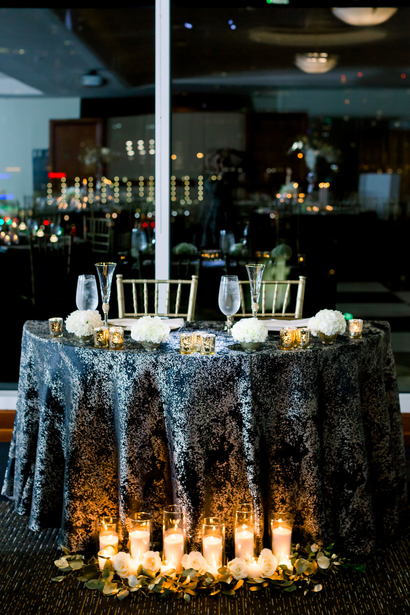 Formal New Year's Eve Wedding Reception Decor, Sweetheart Table with Black and Gold Tablecloth, Romantic Candles and Greenery, Gold Chiavari Chairs | Wedding Photographer Shauna and Jordon Photography | Tampa Bay Wedding Planner UNIQUE Weddings + Events, Wedding Rentals A Chair Affair