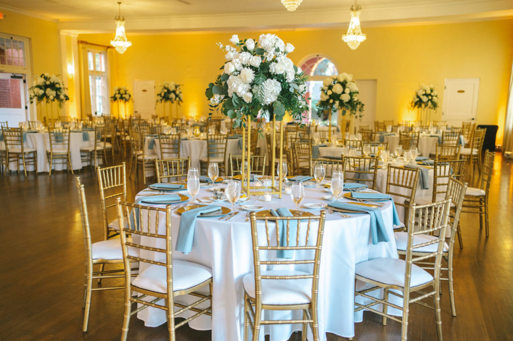 Classic Elegant Ballroom Wedding Reception Decor, Round Tables with White Tablecloths, Dusty Blue Napkin Linens, Gold Chiavari Chairs, Tall Modern Geometric Stand with Lush White Hydrangeas, Roses and Greenery, Eucalyptus Floral Centerpiece | Tampa Bay Wedding Photographer Kera Photography | Outside the Box Rentals | Historic Wedding Venue The Orlo | Wedding Planner Breezin' Weddings