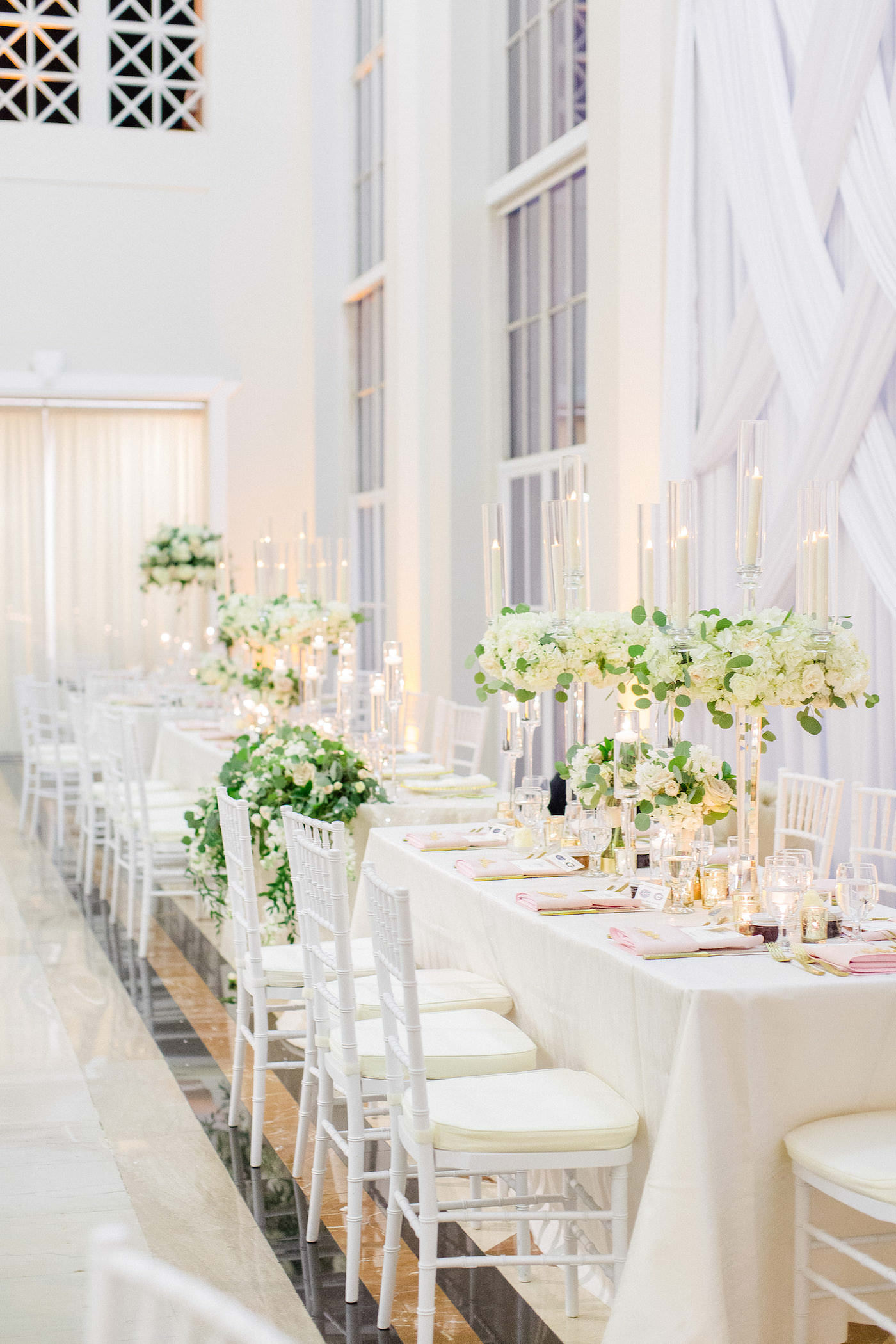 Classic Wedding Reception and Decor, with Long Feasting Tables, White Draping, Tall Floral Centerpieces on Crystal Candelabra with Greenery and Ivory Hydrangea Flowers, White Chiavari Chairs | Downtown Tampa Wedding Venue The Vault | Florida Wedding Planner Breezin' Weddings