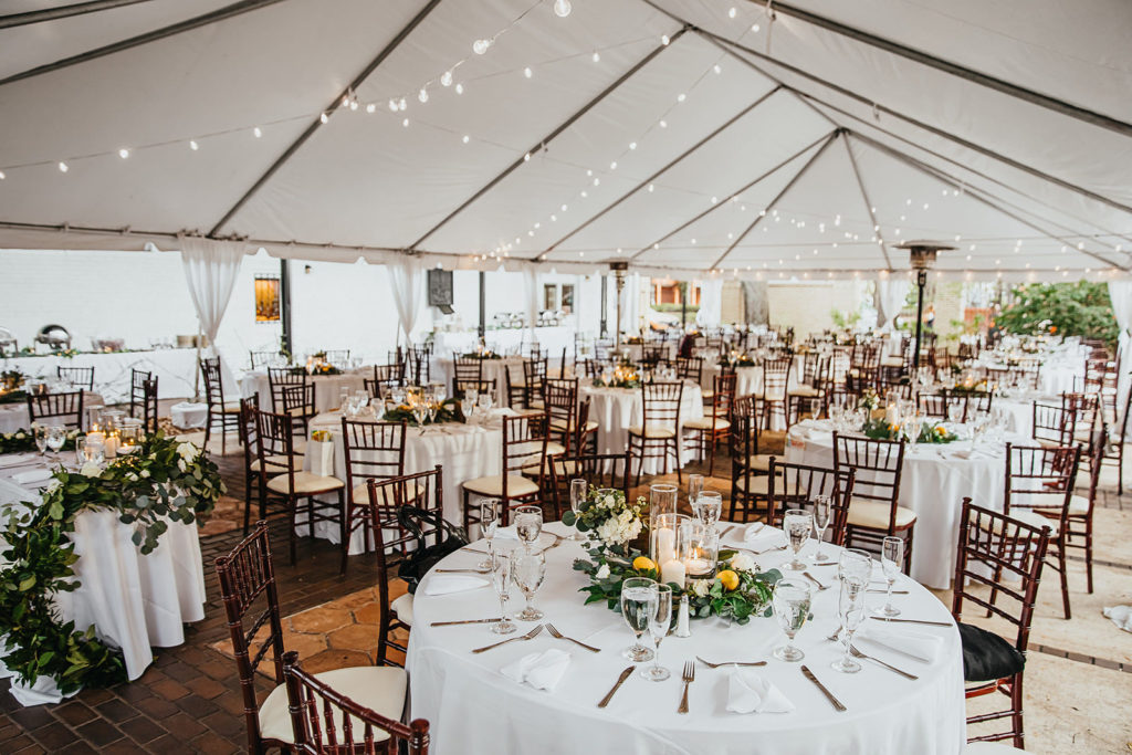 Outdoor Garden Wedding Reception Tent with Canopy String Lights | Round White Tables with Mahogany Wood Chiavari Chairs and Greenery Wreath Centerpieces with Lemons and Hurricane Pillar Candles by Tampa Wedding Florist Monarch Events and Designs