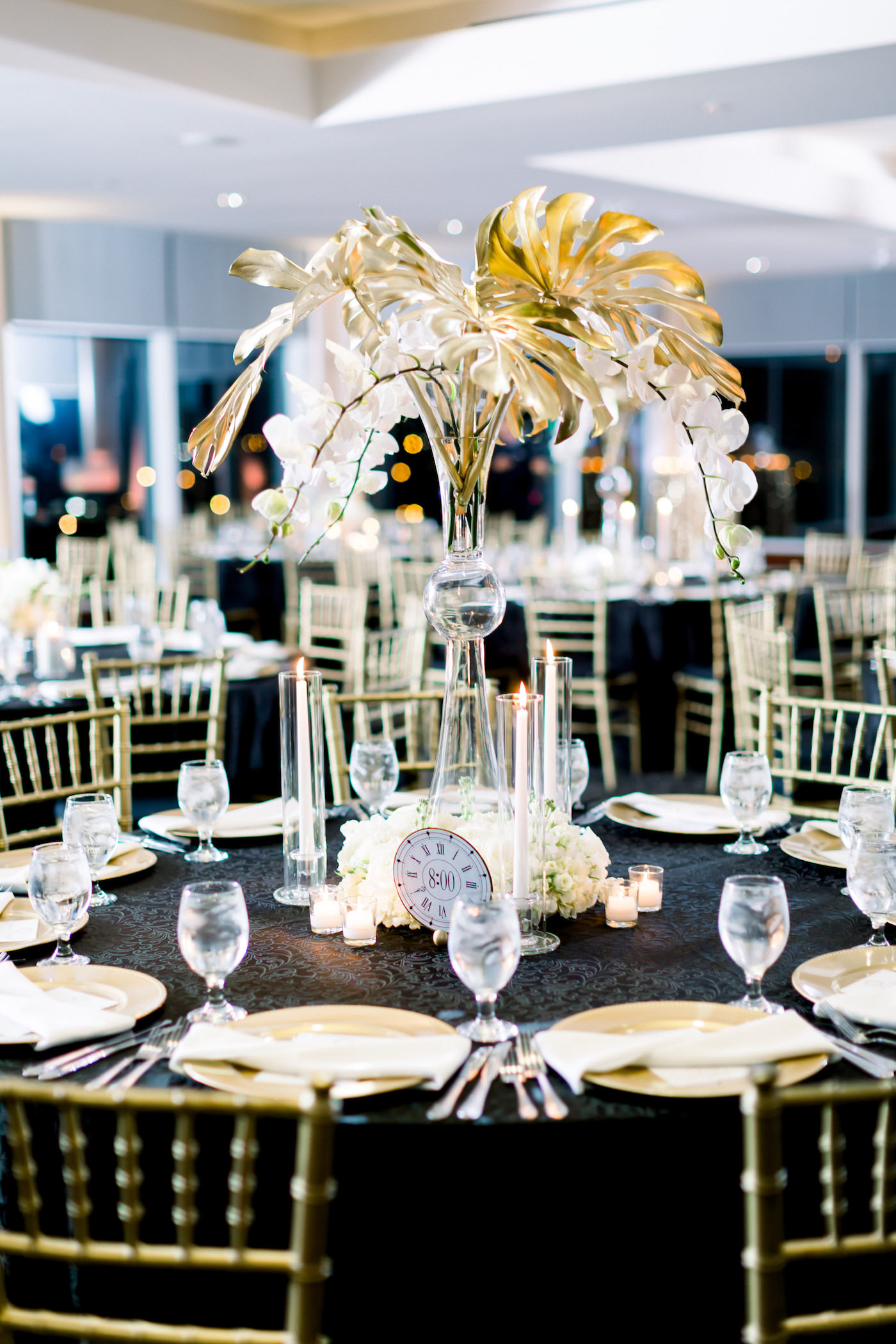 Formal New Year's Eve Wedding Reception Decor, Round Tables with Black Linens, Gold Chiavari Chairs, Tall Vase with Gold Painted Palm Monstera Leaves and White Orchids Centerpieces, White and Gokd Clocks | Wedding Photographer Shauna and Jordon Photography | Tampa Bay Wedding Rentals A Chair Affair | Wedding Planner UNIQUE Weddings + Events