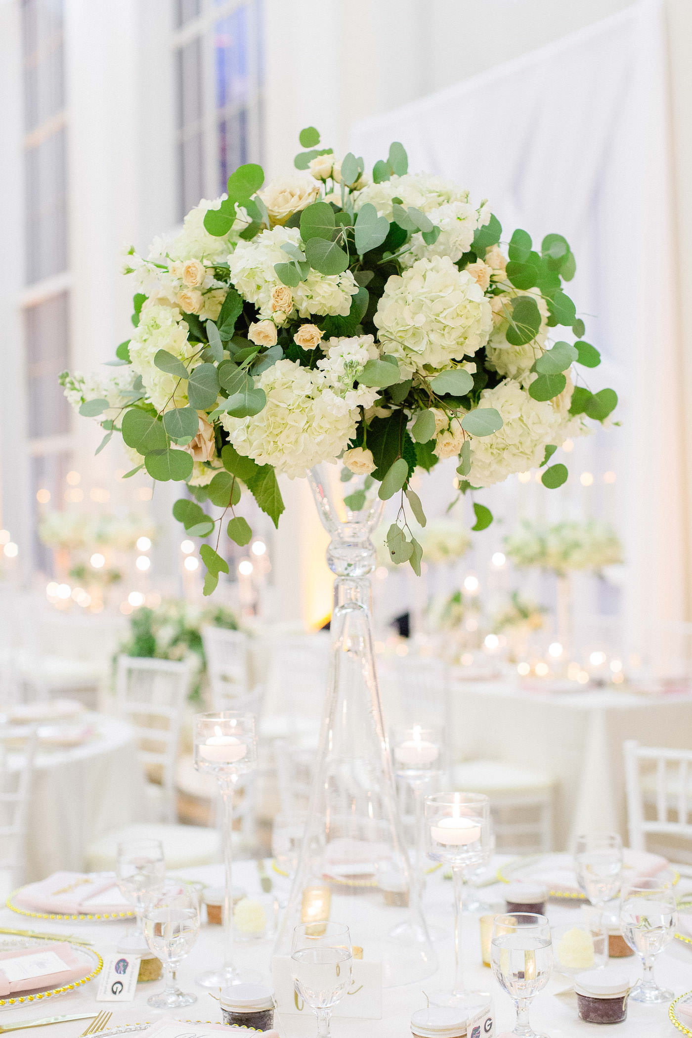 Classic Wedding Reception and Decor, White Criss Cross Draping and Custom Monogram Gobo Light as Backdrop for Sweetheart Table, Lush Greenery Eucalyptus, Ivory Hydrangeas, Blush Pink Roses on Crystal Tall Vase, Ivory Linens | Downtown Tampa Wedding Venue The Vault | Florida Wedding Planner Breezin' Weddings