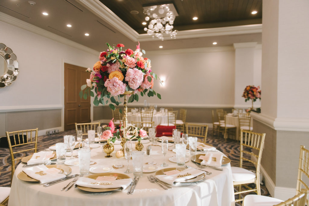 Clearwater Wedding Venue The Hyatt Regency Clearwater Beach Reception Ballroom with White Table Linens and Gold Chiavari Chairs and Gold Charger Plates | Vibrant Bright Colorful Tall Centerpieces with Pink Hydrangea and Orange Roses atop Gold Candlesticks | Gabro Event Services Wedding Rentals