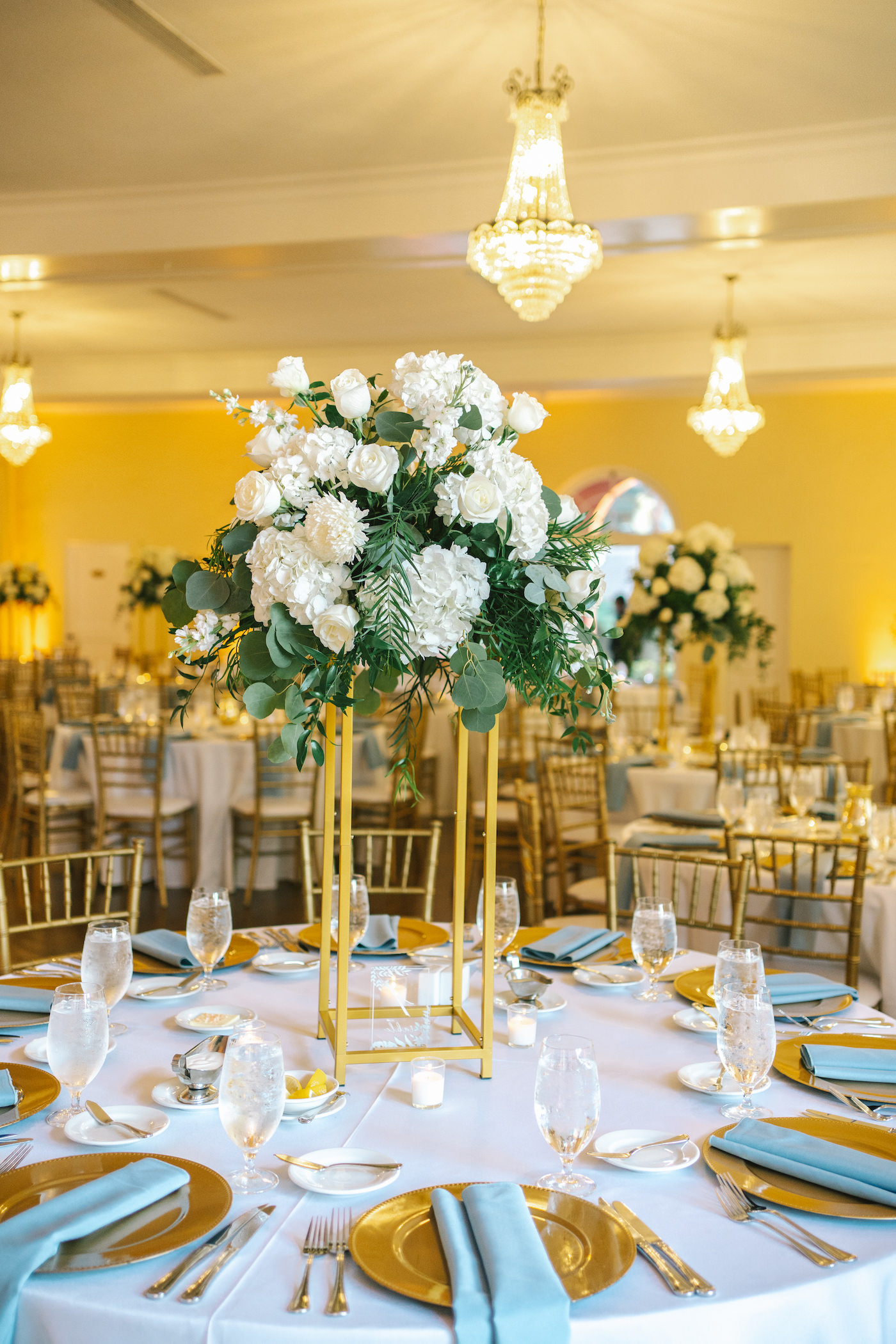 Classic Elegant Wedding Reception Decor Tall Modern Geometric Gold Stand With Lush White Hydrangeas Roses And Greenery Eucalyptus Centerpiece Gold Chargers With Dusty Blue Linen Napkins Tampa Bay Wedding Photographer Kera