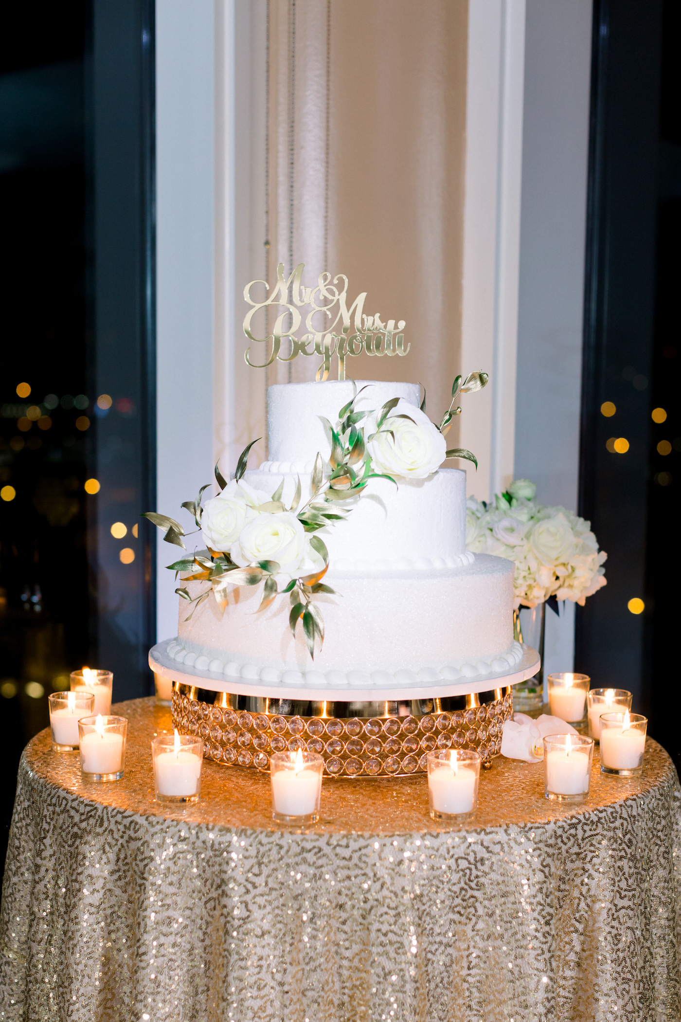 Classic Three Tier White Wedding Cake with Roses and Custom Gold Cake Topper on Table with Gold Sequin Tablecloth and Candles | Wedding Photographer Shauna and Jordon Photography | Tampa Bay Wedding Planner UNIQUE Weddings + Events