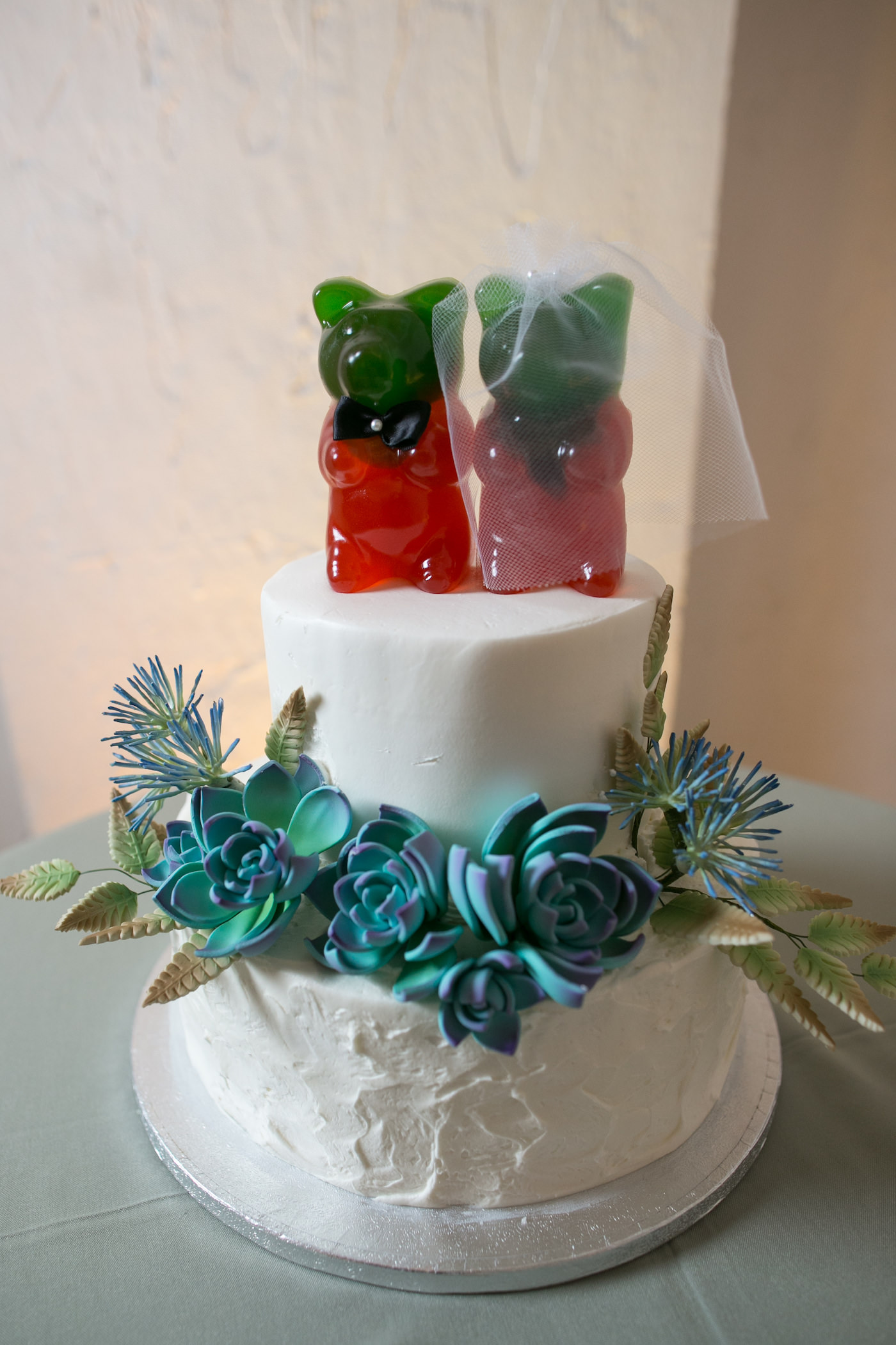 Two Tier White Wedding Cake With Succulent Sugar Flowers And Red And Green Bride And Groom Gummy Bear Cake Topper Wedding Photographer Carrie Wildes Photography Tampa Wedding Planner Unique Weddings