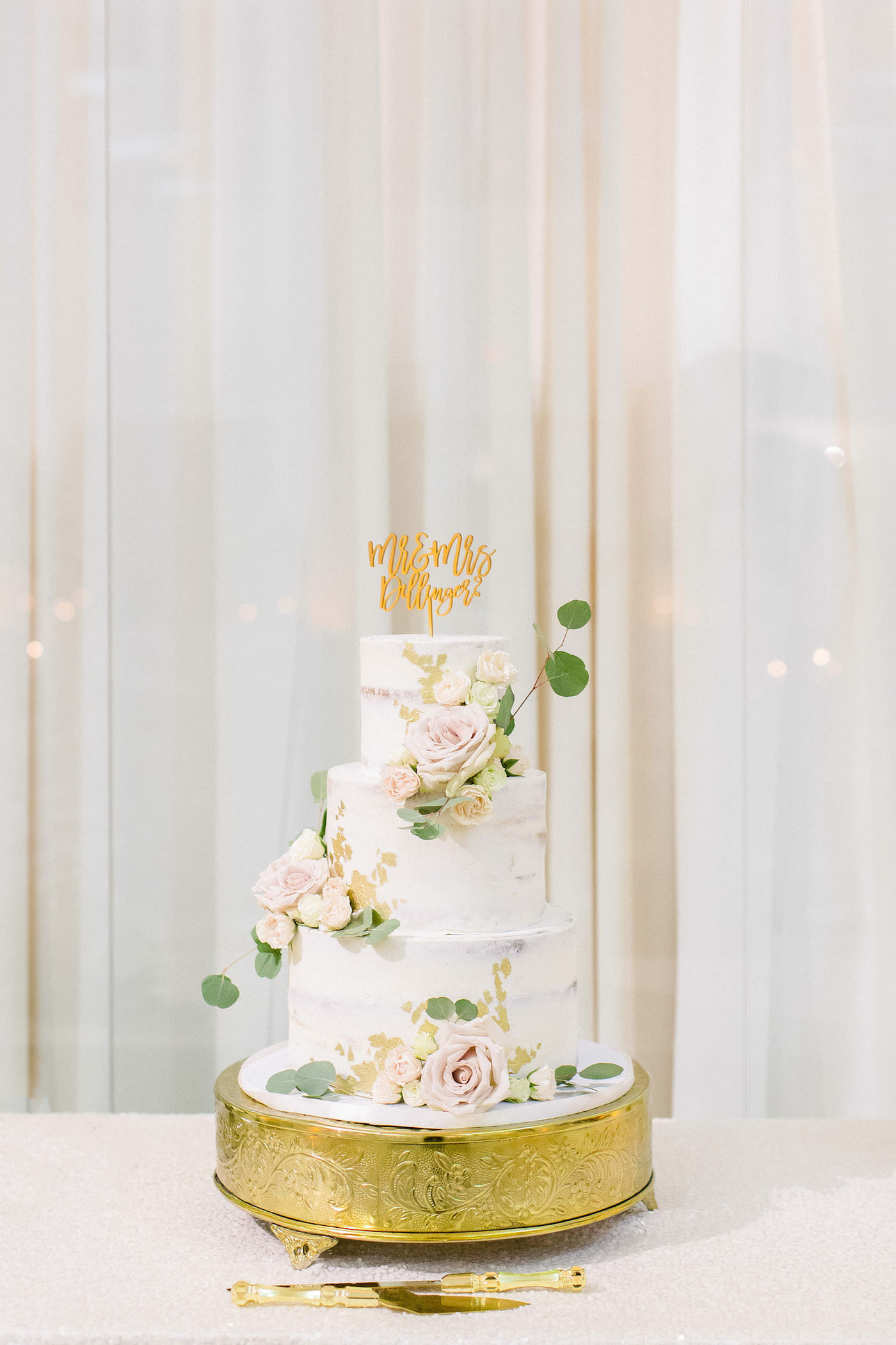 Classic Three Tier White Wedding Cake, Semi Naked Frosted Cake with Gold Foil Detailing, Blush Pink Roses Florals with Greenery Eucalyptus, Custom Gold Cake Topper and Serving Set | Tampa Bay Wedding Planner Breezin' Weddings