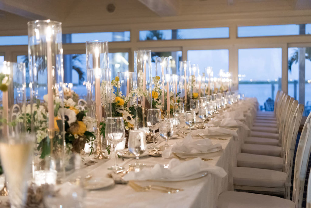 Elegant Nautical Wedding Reception Decor, Long Feasting Table with White Linens, Gold Flatware, Gold Candlesticks, Yellow, White and Greenery Low Floral Centerpieces | Tampa Bay Wedding Planner Parties A'la Carte | Clearwater Wedding Venue Carlouel Yacht Club