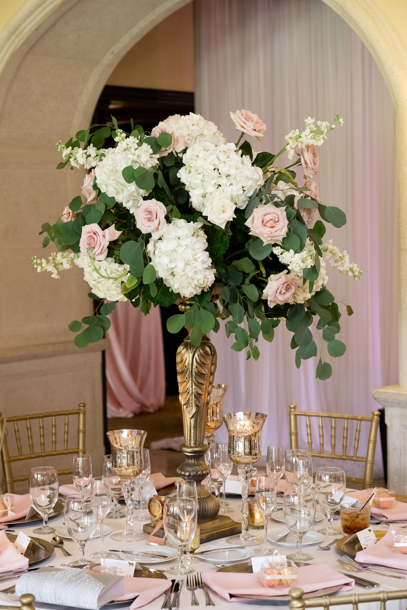 Wedding Reception Table With Blush Pink Napkins On Gold Charger Plates And Tall Gold Candlestick Loose Floral Centerpiece Featuring Blush Pink Roses And Ivory Hydrangea With White Stock And Eucalyptus Greenery