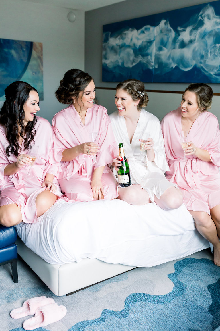 Tampa Bride and Bridesmaids in Pink Robes Champagne Cheers Getting Wedding Ready Hotel Portrait | Wedding Photographer Shauna and Jordon Photography | Wedding Hair and Makeup Femme Akoi Beauty Studio