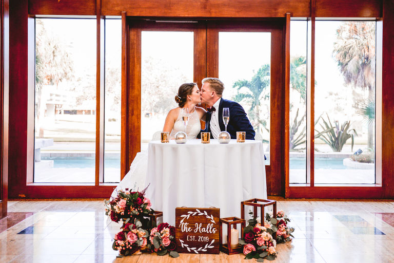 St. Pete Wedding Venue The Poynter Institute | Bride and Groom Sweetheart Table with Wood Lanterns and Candles and Blush Pink and Red Bouquets