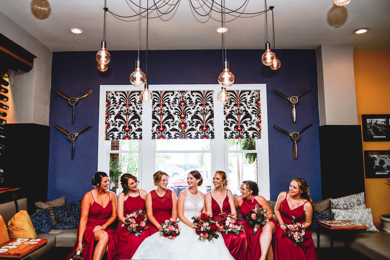 Bride and Bridesmaids Hotel Lobby Portraits | Mismatched Deep Red Maroon Berry Azazie Bridesmaid Dresses with Red and Pink Bouquets