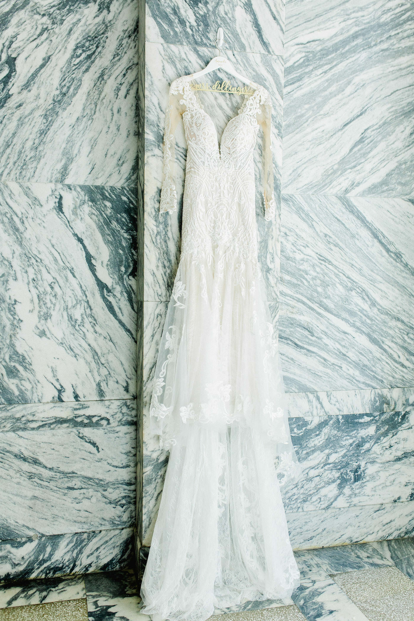 Elegant Illusion Lace Sleeve Deep Sweetheart Neckline Fit and Flare Tulle Skirt Wedding Dress against Marble Wall of Le Meridien Hotel in Downtown Tampa | Florida Wedding Planner Breezin' Weddings