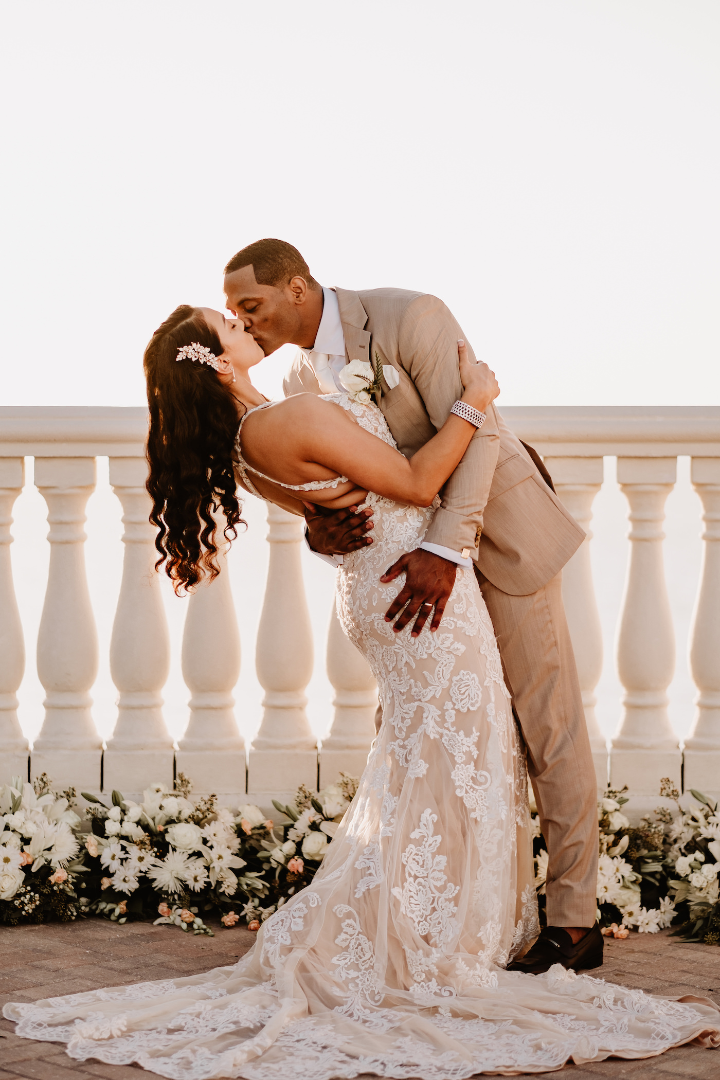 Bride and Groom First Kiss at Clearwater Wedding Venue Hyatt Regency Clearwater Beach Hotel   Outdoor Rooftop Waterfront Wedding Portrait   Champagne Lace Sheath Illusion Neck Bridal Gown with Criss Cross Back Straps   Groom Khaki Tan Suit