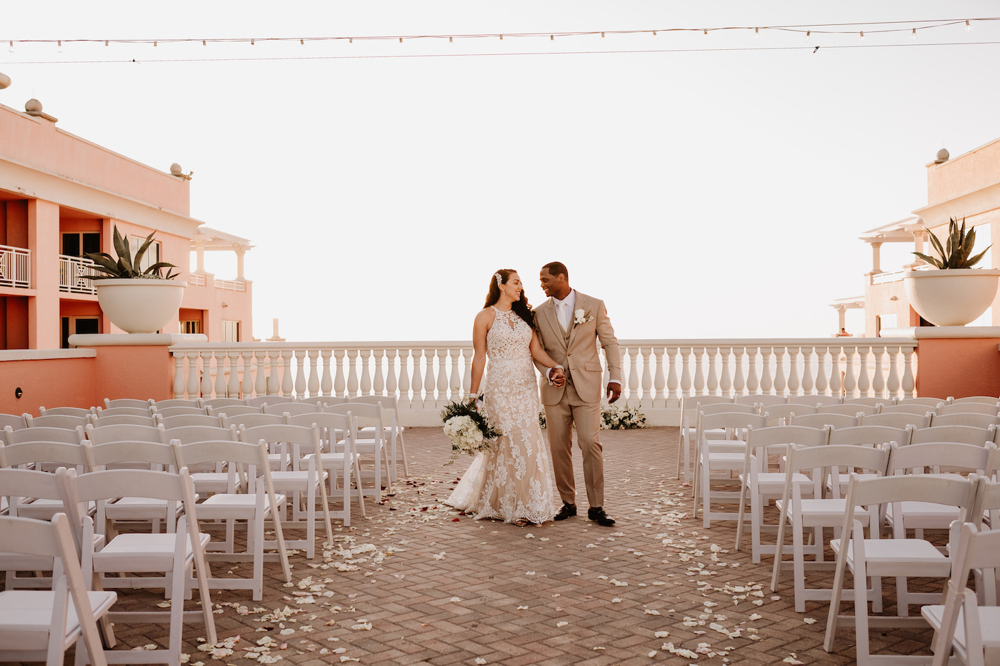 Bride and Groom Portrait at Clearwater Wedding Venue Hyatt Regency Clearwater Beach Hotel   Outdoor Rooftop Waterfront Wedding with White Garden Chairs   Champagne Lace Sheath Illusion Neck Bridal Gown   Groom Khaki Tan Suit