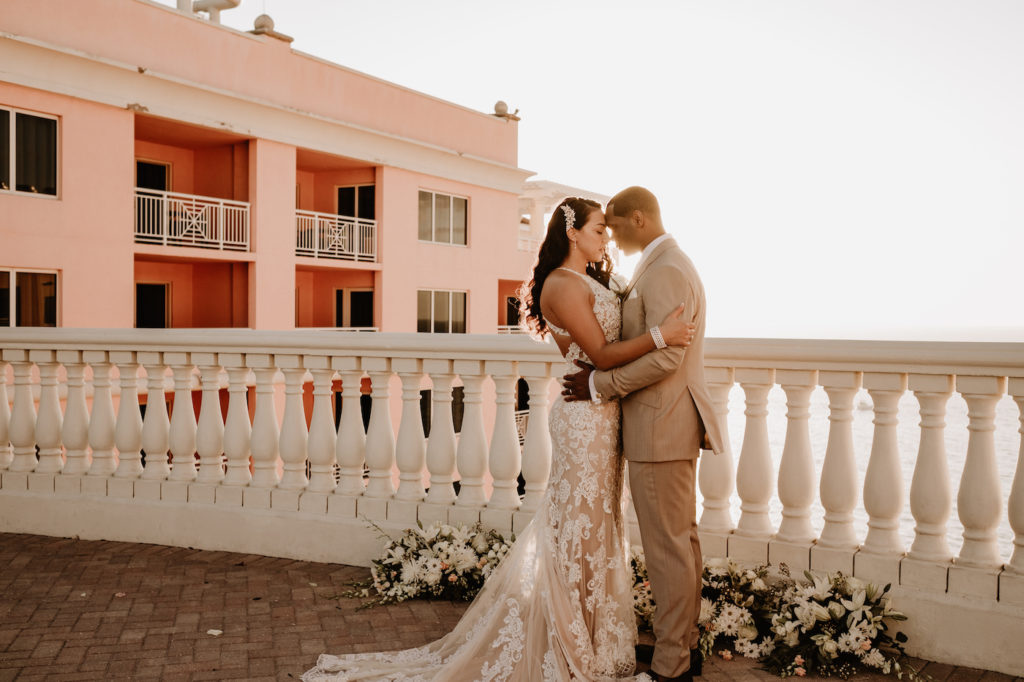 Bride and Groom Portrait at Clearwater Wedding Venue Hyatt Regency Clearwater Beach Hotel | Outdoor Rooftop Waterfront Wedding | Champagne Lace Sheath Illusion Neck Bridal Gown | Groom Khaki Tan Suit
