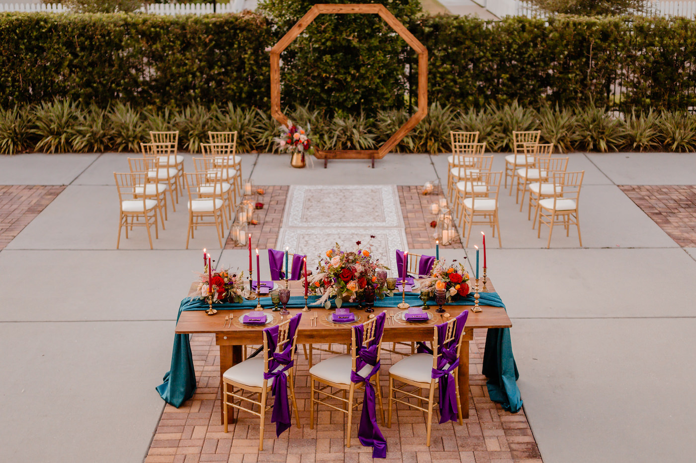 Boho Glam Wedding Ceremony Backdrop with Wood Geometric Arch and Gold Chiavari Chairs and Rug Runner | Colorful Orange Pink and Red Floral Centerpiece with Pampas Grass | Tampa Wedding Florist Monarch Events and Designs | Wood Farm Table with Teal Turquoise Runner and Colorful Taper Candles and Purple Chair Sashes