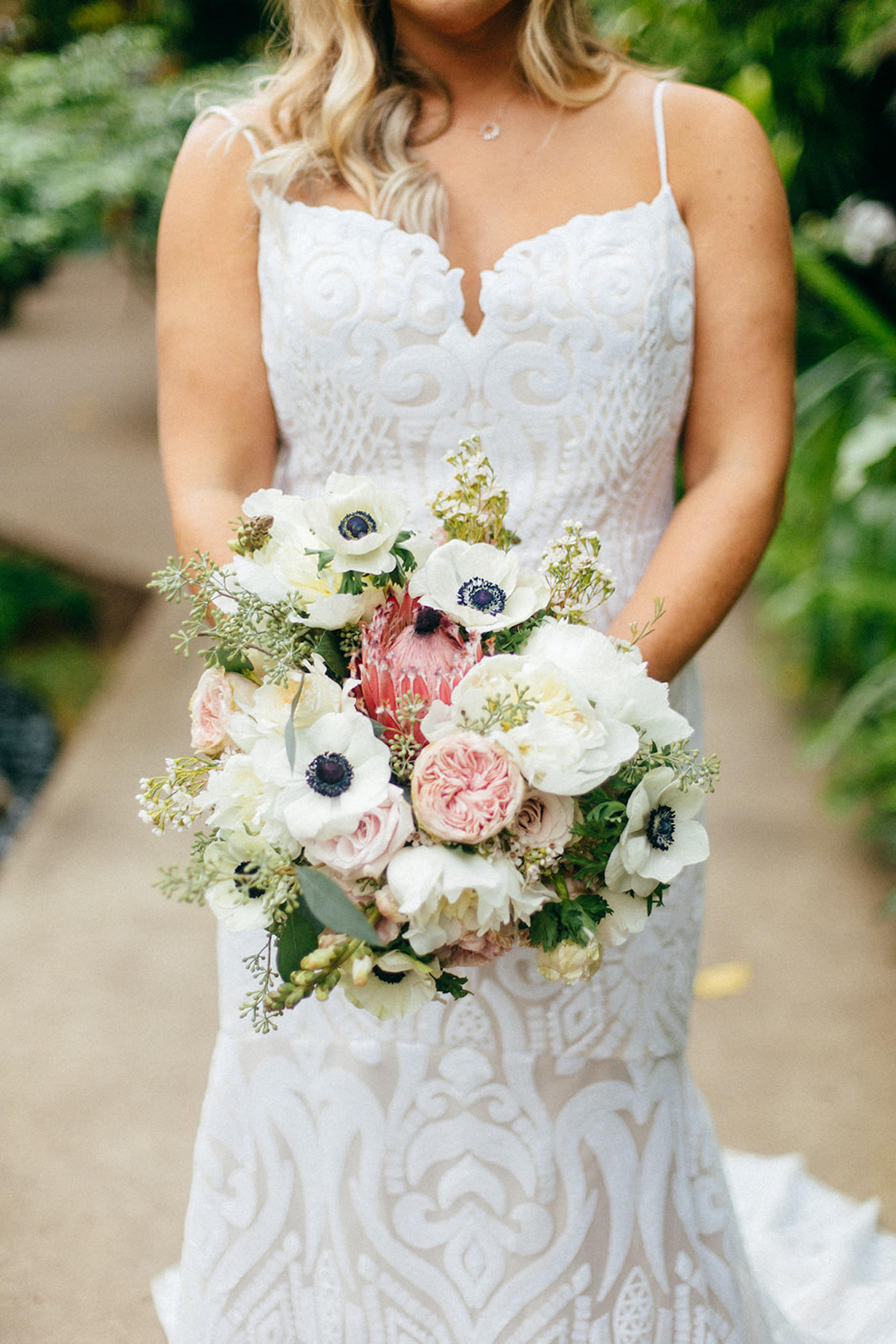 Romantic Florida Bride Holding Garden Inspired Wedding Bouquet with Light Pink Peonies, Blush King Protea, Bride Wearing Hayley Paige Lace Wedding Dress