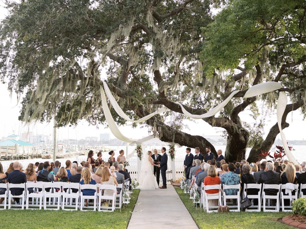 Wedding Ceremony Tree Fabric Swag by Tampa Wedding Florist Brides N Blooms | Florida Fall Autumn Wedding Waterfront Venue with White Garden Chairs