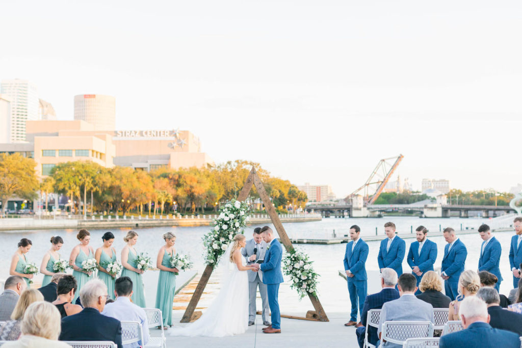 Boho Chic Waterfront Wedding Ceremony Portrait of Bride and Groom Exchanging Wedding Vows, Wooden Triangular Arch with Lush Greenery and Ivory, White Roses, Bridesmaids in Green Dresses | Wedding Venue Tampa River Center | Wedding Florist Bruce Wayne Florals | Wedding Planner Parties A'la Carte