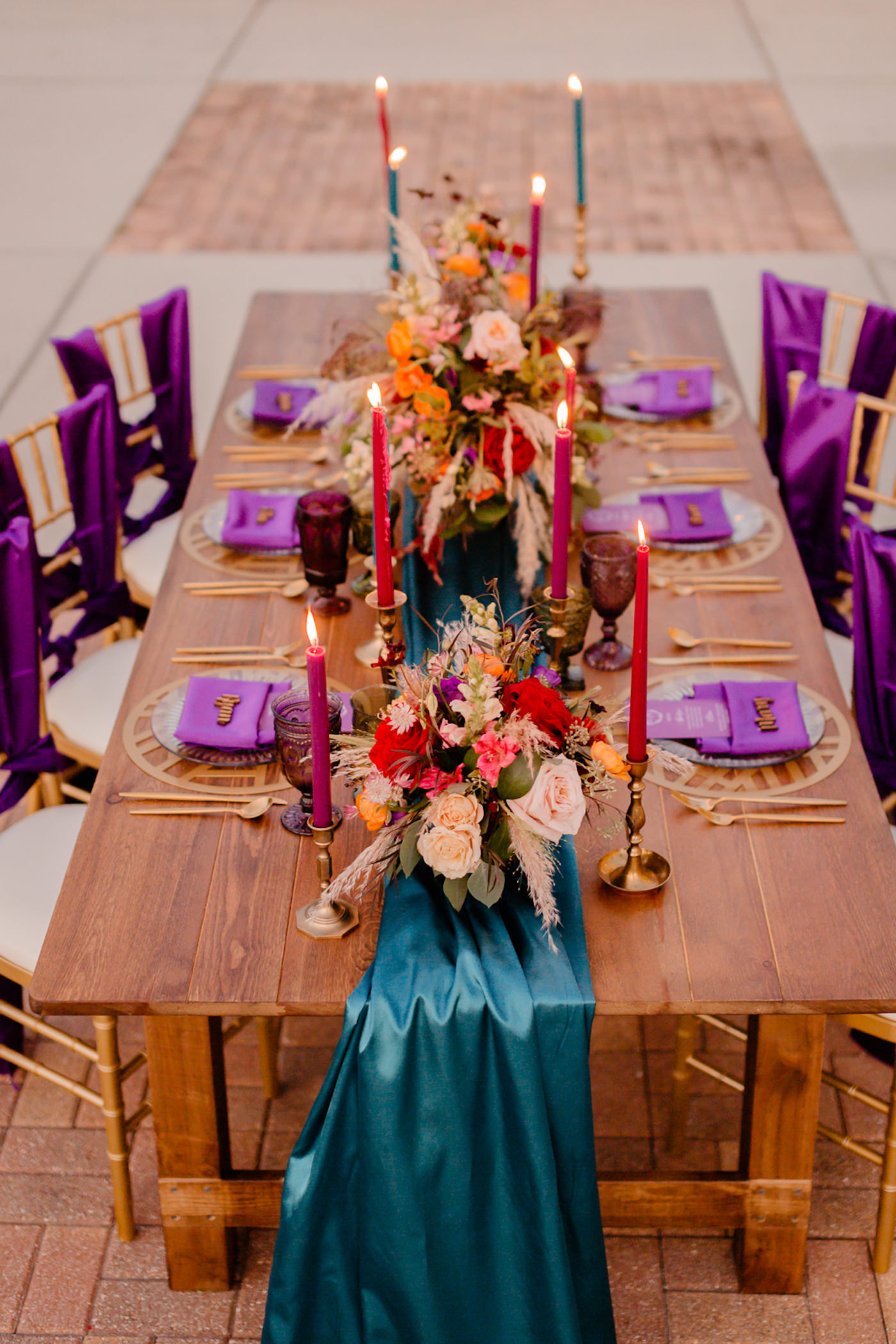 Boho Glam Wedding Reception Table with Orange Pink and Red Floral Arrangement Centerpiece with Pampas Grass | Tampa Wedding Florist Monarch Events and Designs | Wood Farm Table with Teal Turquoise Runner and Colorful Taper Candles and Purple Sashes on Gold Chiavari Chairs
