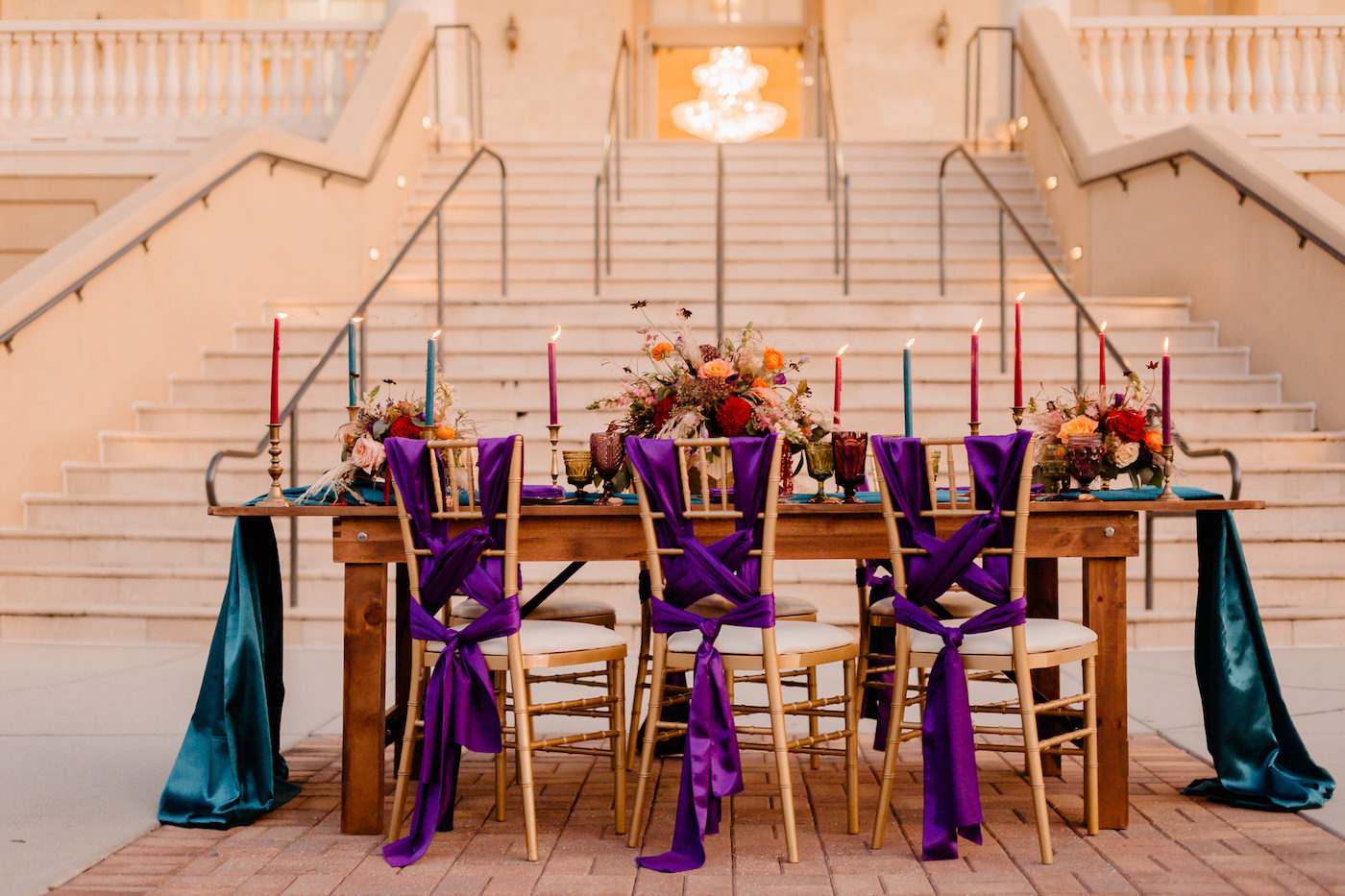 Boho Glam Wedding Reception Table with Orange Pink and Red Floral Arrangement Centerpiece with Pampas Grass | Tampa Wedding Florist Monarch Events and Designs | Wood Farm Table with Teal Turquoise Runner and Colorful Taper Candles and Purple Sashes on Gold Chiavari Chairs | Tampa Wedding Venue The Regent Grand Staircase and Columns