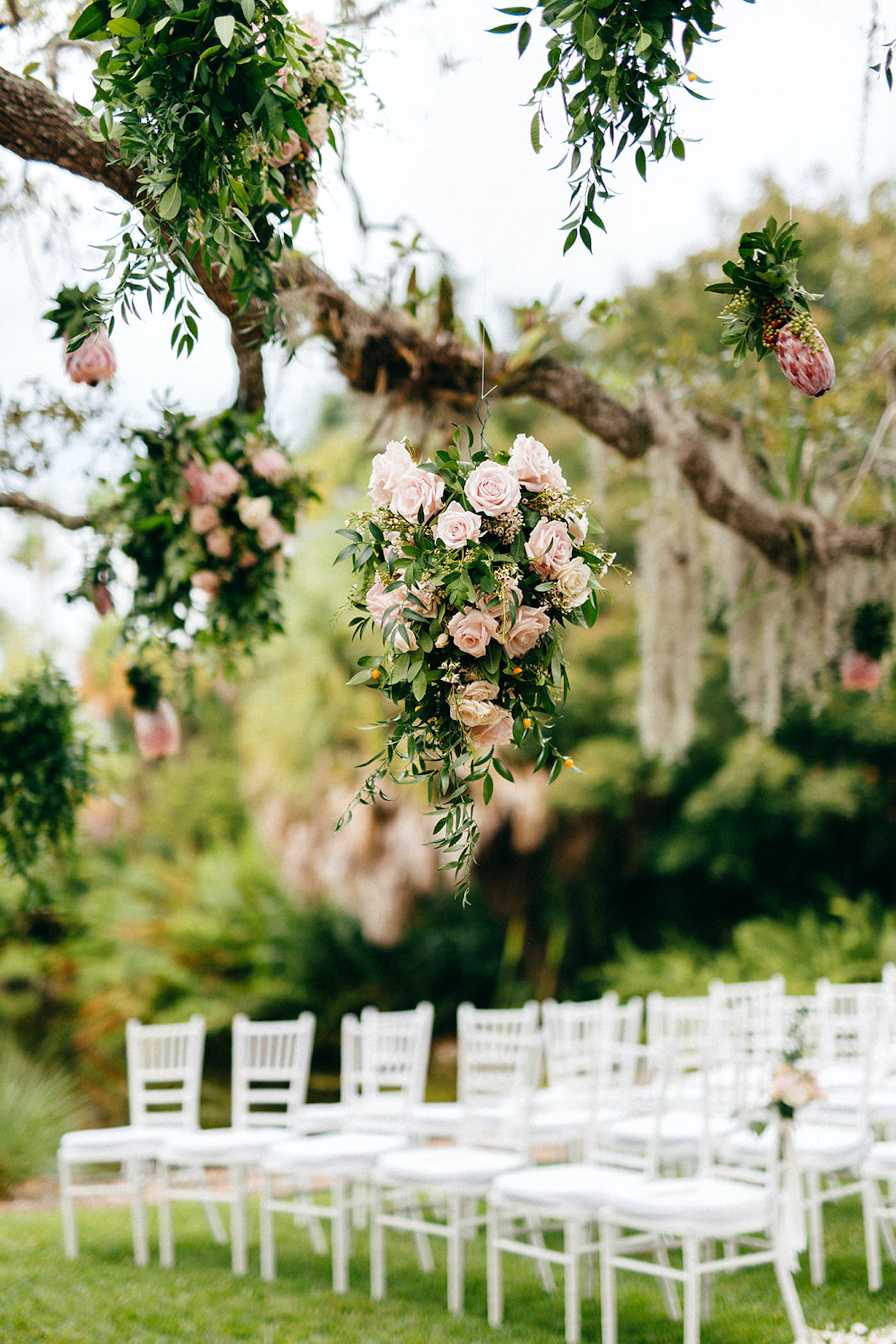 Romantic, Garden Inspired Wedding Ceremony, Large Floral Decor Hanging From Tree Branches Outside, Blush Pink Roses and Peonies, with Greenery, White Chiavari Chairs   Florida Wedding Planner NK Weddings   Marie Selby Botanical Gardens