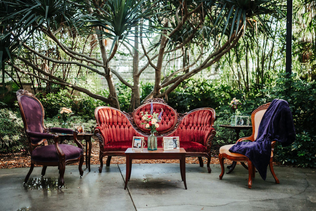 Antique Cocktail Lounge Seating, Red Velvet Love Seat, Purple Velvet Chair and Ivory Chair with Plum Blanket, Wooden Coffee Table with Colorful Floral Arrangement | St. Pete Wedding Venue Sunken Gardens