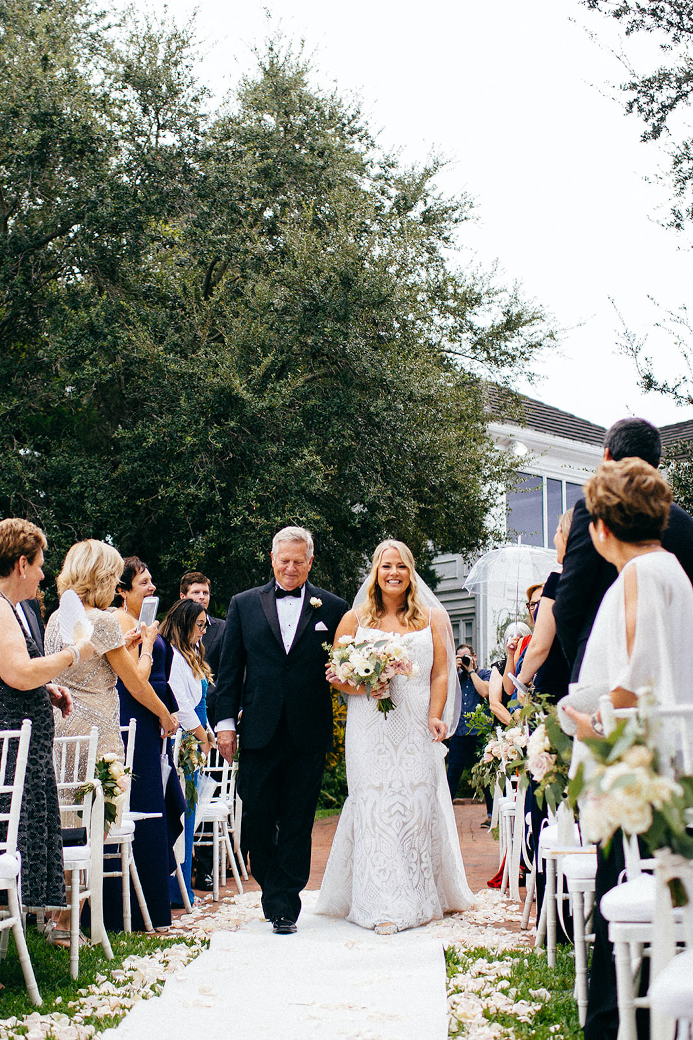 Florida Bride and Father Walk Down the Aisle During Wedding Processional, Bride Wearing Hayley Paige Wedding Dress, Walking on White Aisle Runner Decorated With Scattered Petals   Sarasota Wedding Planner NK Weddings