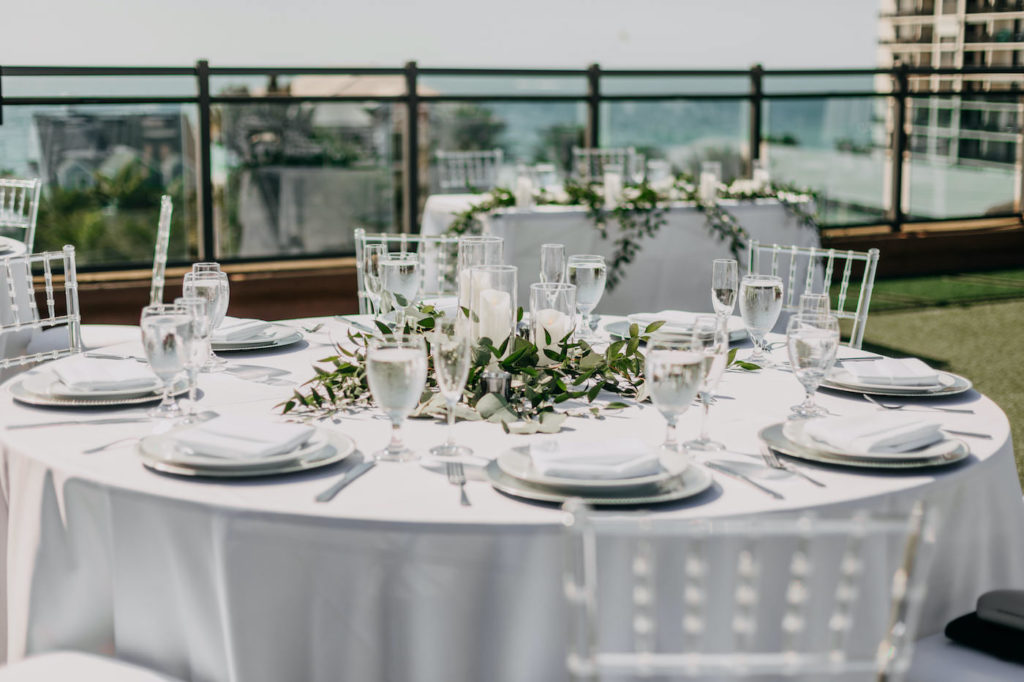 Classic Florida Waterfront Rooftop Reception Decor | Round Tables with White Linens, Clear Acrylic Ghost Chairs, Low Floral Centerpieces of Candles and Greenery | Gulf Coast Boutique Hotel and Wedding Venue The Hotel Zamora | St. Pete Beach Wedding Planner Blue Skies Weddings and Events | Tampa Bay Rental Company Gabro Event Services | Wedding DJ Grant Hemond and Associates