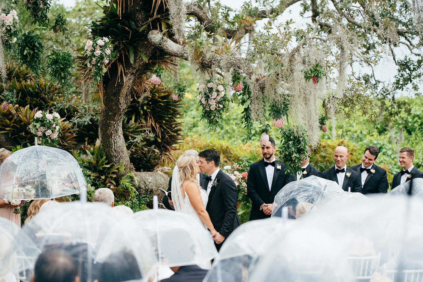 Romantic Florida Wedding Outside in Garden Inspired Ceremony Under Large Tree with Hanging Moss, Guests with Clear Umbrellas In the Rain   Sarasota Wedding Planner NK Weddings