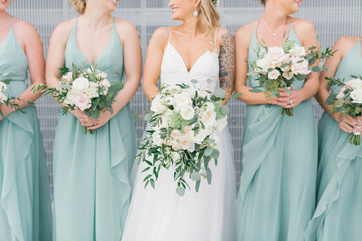 Boho Chic Bride in A-Line V Neckline Spaghetti Strap Wedding Dress with Tulle Skirt, Bridesmaids in Matching Sage Green Dresses Holding Ivory Roses and Greenery Floral Bouquets | Tampa Bay Wedding Florist Bruce Wayne Florals