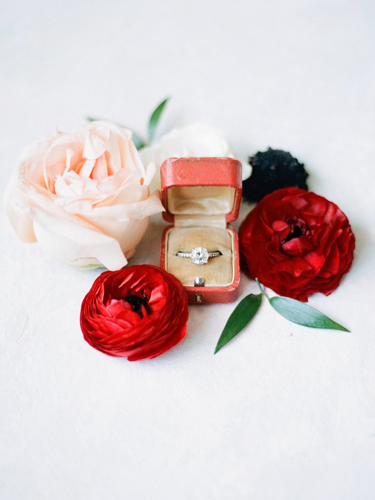 Fall Autumn Wedding Ring Box Shot with Red Ranunculus and Cream Rose | Red Cartier Engagement Ring Box with Round Solitaire Diamond and Channel Set Band | Brides N Blooms