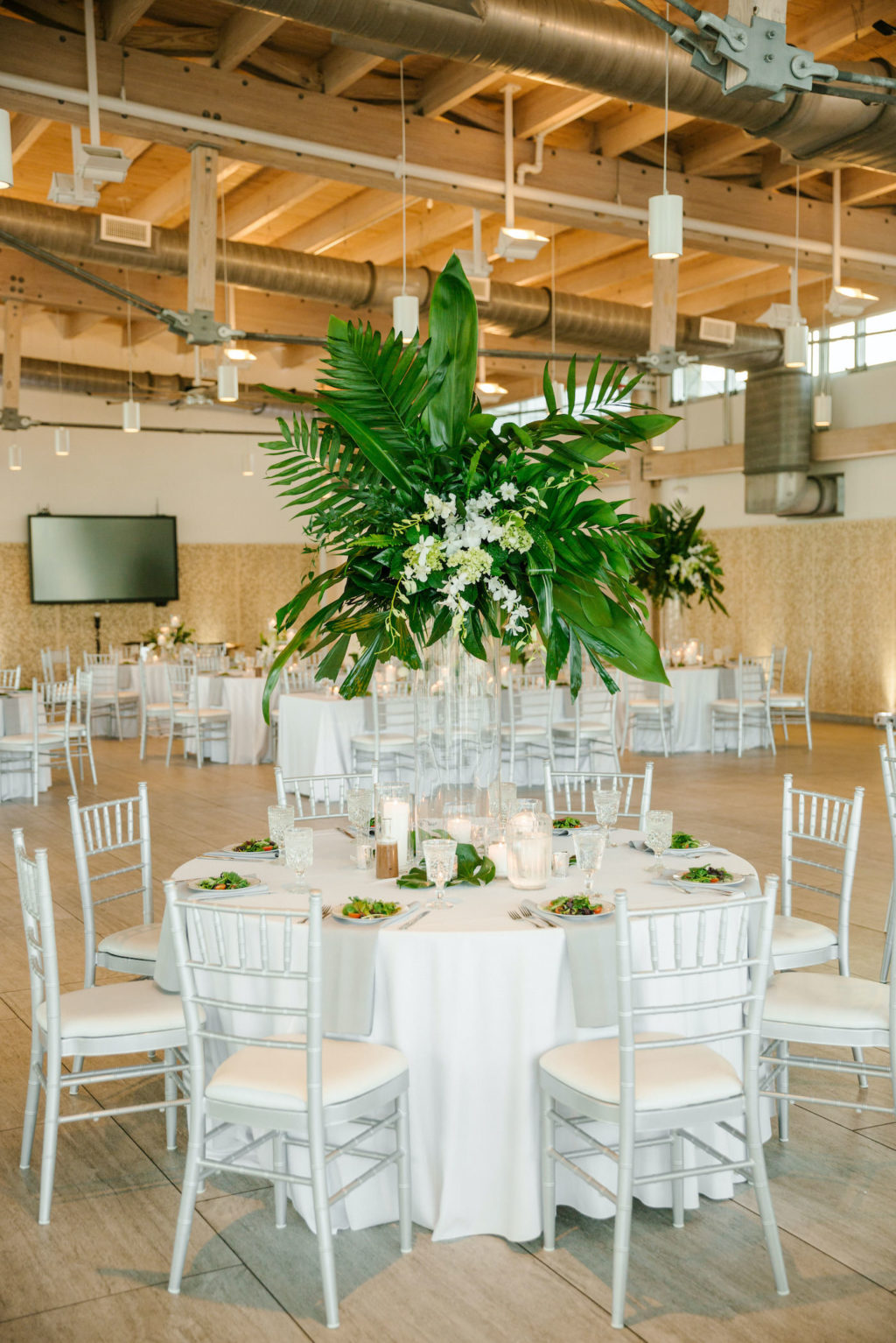 Tropical Tampa Florida Wedding Reception | White Wedding Reception Table with Silver Chiavari Chairs and Tall Tropical Palm Leaf Centerpiece with White Orchids | Tampa Wedding Florist Bruce Wayne Florals
