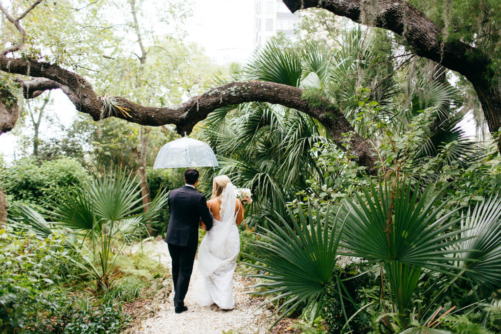 Florida Bride and Groom Strolling In the Rain, Under Clear Umbrella   Sarasota Wedding Planner NK Weddings   Marie Selby Botanical Gardens