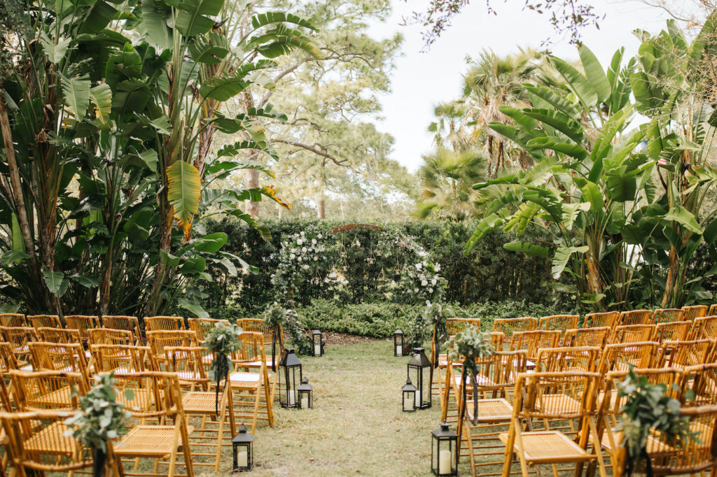 Boho Chic Outdoor Wedding Ceremony at Tampa Garden Club Venue | Natural Wood Bamboo Chairs with Black Lanterns and Eucalyptus Greenery Aisle Markers | Round Wood Moon Arch Ceremony Backdrop with Suspended Geometric Containers and Eucalyptus Greenery Garland Floral Arrangements | Winsor Event Studio