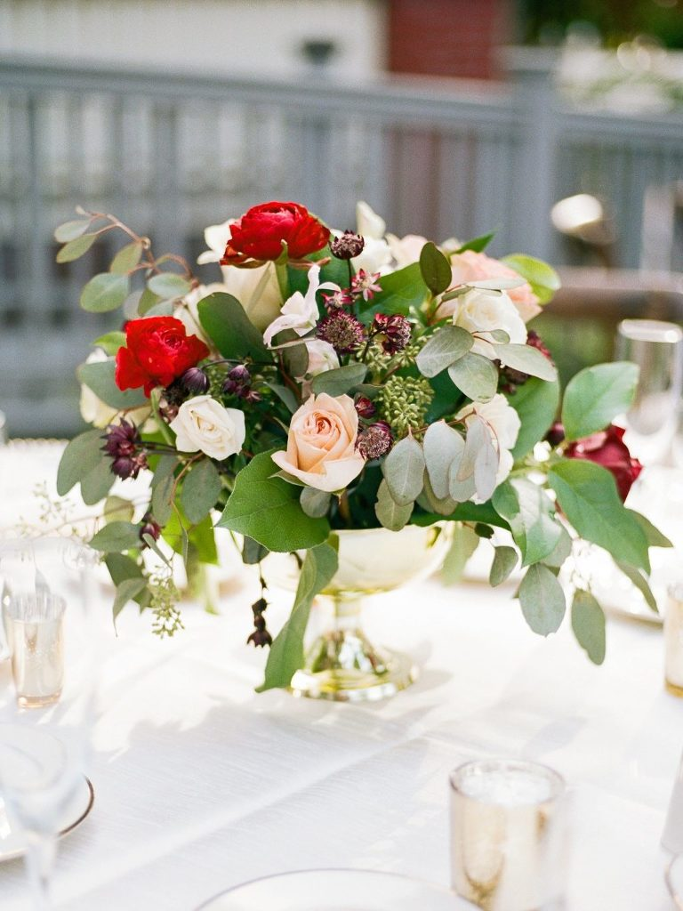 Low Wedding Centerpiece Floral Arrangement of Eucalyptus Greenery, Cream Roses, Red Renunculus, and Bordeaux Chrysanthemums in Gold Pedestal Vase | Tampa Wedding Florist Brides N Blooms