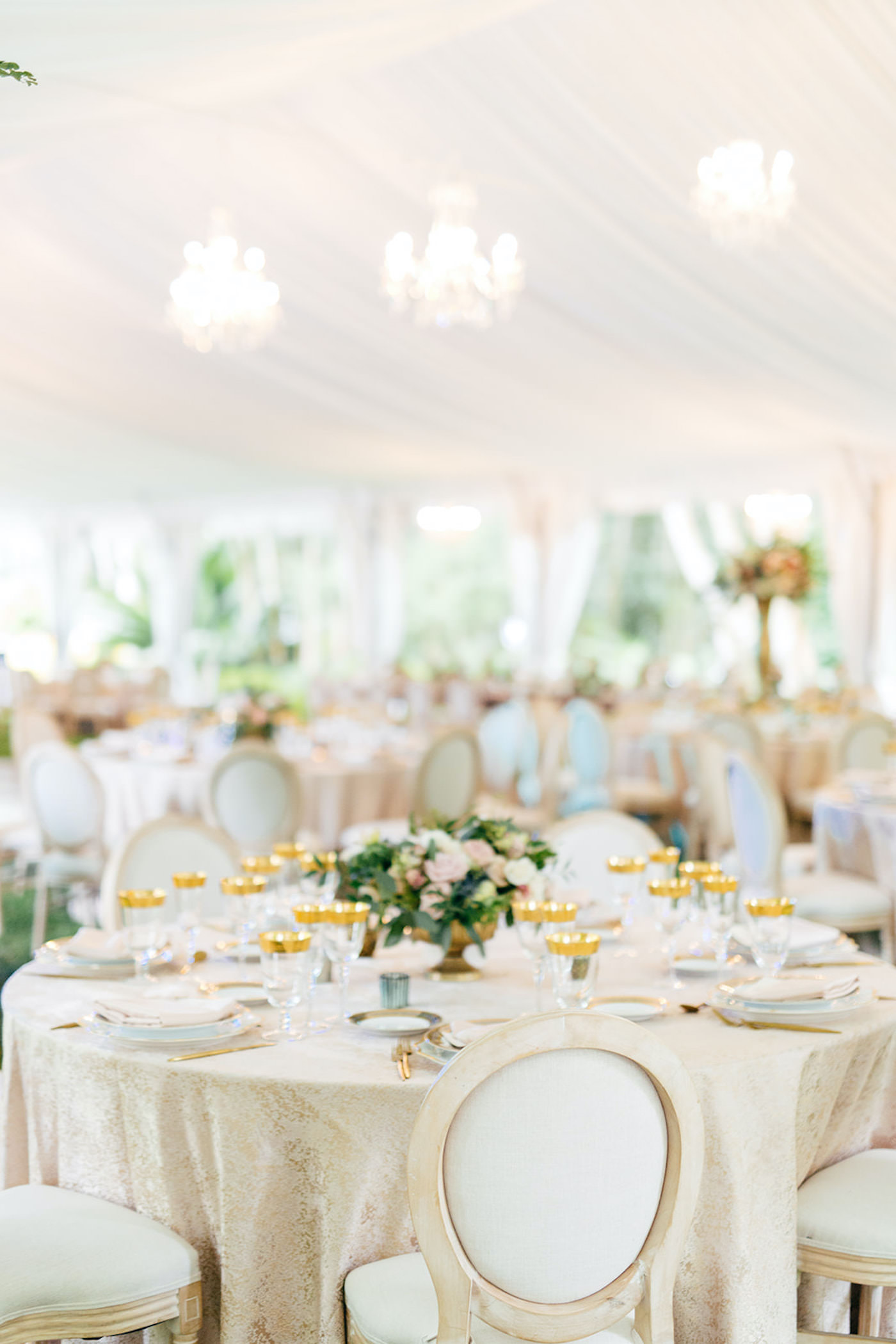 Romantic, Garden Inspired Wedding Reception Decor In White Tented Outdoor Florida Wedding, Round Tables with Gold Linens,Modern Circle Back Chairs, Gold Accented Table Setting, Chandelier, Low Floral centerpiece with Blush Pink Flowers and Greenery   Sarasota Wedding Planner NK Weddings