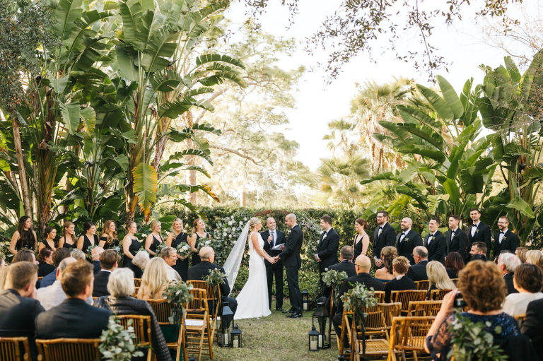 Bride and Groom Exchanging Vows during Boho Chic Outdoor Wedding Ceremony at Tampa Garden Club Venue | Natural Wood Bamboo Chairs with Black Lanterns and Eucalyptus Greenery Aisle Markers | Round Wood Moon Arch Ceremony Backdrop with Suspended Geometric Containers and Eucalyptus Greenery Garland Floral Arrangements | Black and White Wedding with Bridesmaids in Black Dresses and Groomsmen in Black Tux Suit
