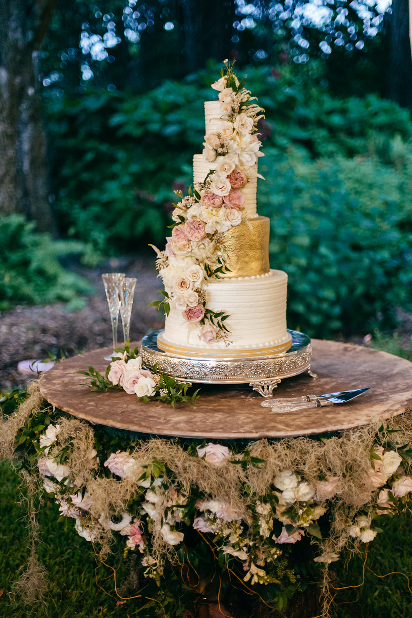 Romantic, Garden Inspired Wedding Cake, 5 Tier Wedding Cake for 200, Gold Icing, Floral Accents with Blush Pink Roses and Ivory Flowers Cascading Down the Cake, Cake Table Decorated with Greenery and Banyan Tree Moss   Florida Wedding Planner NK Weddings