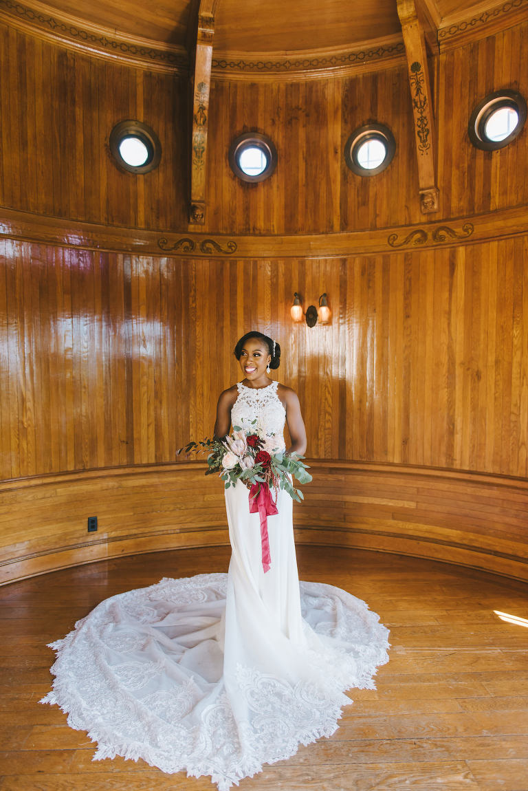Romantic Florida Bride Holding Luxurious Bridal Bouquet, Bride Wearing Form Fitting Lace Wedding Dress, Holding Red, Pink, Ivory and White Floral Bouquet with Burgundy Ribbon, Inside Historic Powel Crosley Estate in Sarasota | Florida Wedding Photographer Kera Photography