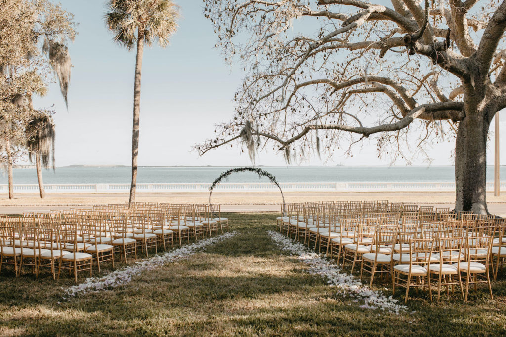 Tampa Wedding Venue The Tampa Garden Club Outdoor Lawn Reception overlooking Tampa Bay Bayshore Water View | Gold Chiavari Chairs and Ivory Rose Petals Aisle with Metal Round Moon Arch