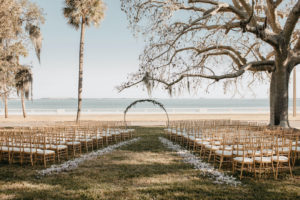 Tampa Wedding Venue The Tampa Garden Club Outdoor Lawn Reception overlooking Tampa Bay Bayshore Water View   Gold Chiavari Chairs and Ivory Rose Petals Aisle with Metal Round Moon Arch