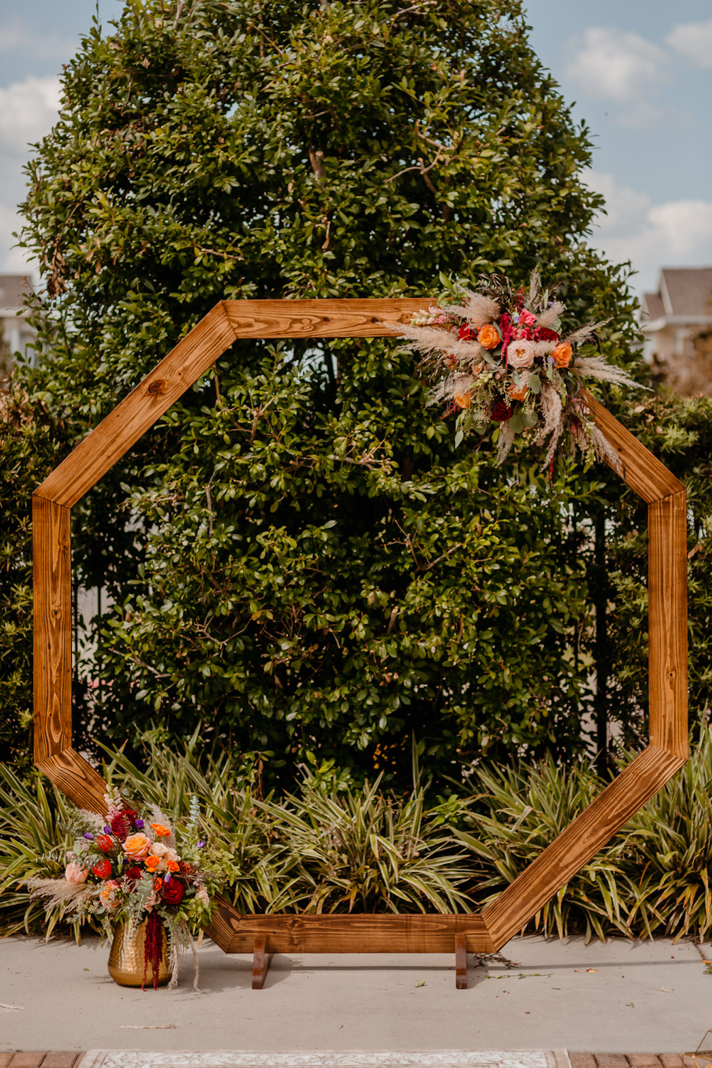 Boho Glam Wedding Ceremony Backdrop with Wood Geometric Arch and Colorful Orange Pink and Red Floral Arrangements with Pampas Grass | Tampa Wedding Florist Monarch Events and Designs