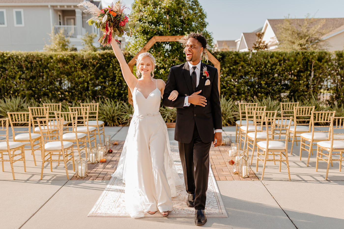 Boho Glam Wedding Ceremony Backdrop with Wood Geometric Arch and Gold Chiavari Chairs and Rug Runner | Colorful Orange Pink and Red Bouquet with Pampas Grass | Tampa Wedding Florist Monarch Events and Designs | Embroidered Floral Lace V Neck Bridal Gown and Groom in Classic Black Tux