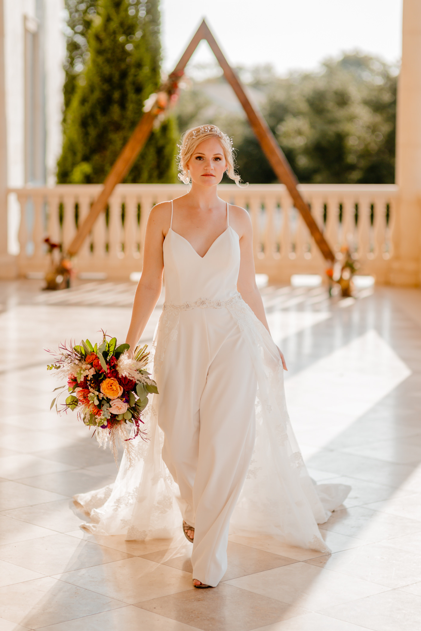 Boho Glam Wedding Ceremony Backdrop with Wood Geometric Arch | Colorful Orange Pink and Red Bouquet with Pampas Grass | Tampa Wedding Florist Monarch Events and Designs | Embroidered Floral Lace V Neck Bridal Gown